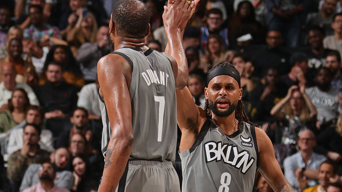 Kevin Durant #7 and Patty Mills #8 of the Brooklyn Nets high five against the Washington Wizards