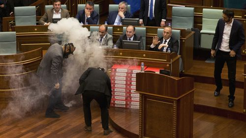 Despite the use of the tear gas, the Kosovo parliament ultimately passed the bill 80-11 with the minimum two-thirds required. Picture: AAP.