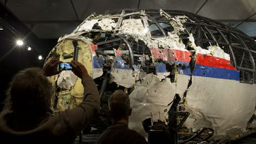 People take photos of the reassembled fuselage of MH17. (AAP)
