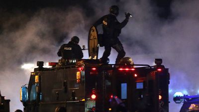 A police officer is about to throw a tear gas canister as police try to disperse demonstrators who are protesting the shooting death of Michael Brown in Ferguson, Missouri. (AAP)