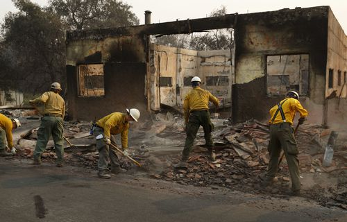 Fire crews clear rubble from the road near a building burned in Paradise.