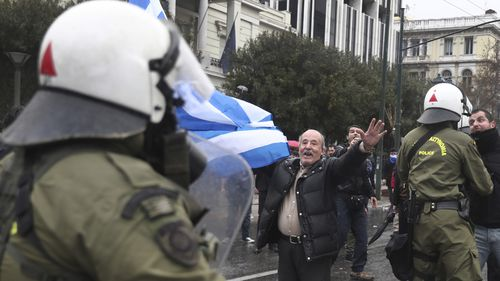 A man holding a Greek flag shouts slogans during clashes with riot police after a rally in Athens, Sunday, Jan. 20, 2019.