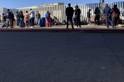 Para migran menunggu untuk menyeberang ke Amerika Serikat menunggu berita di perlintasan perbatasan Rabu 17 Februari 2021 di Tijuana.