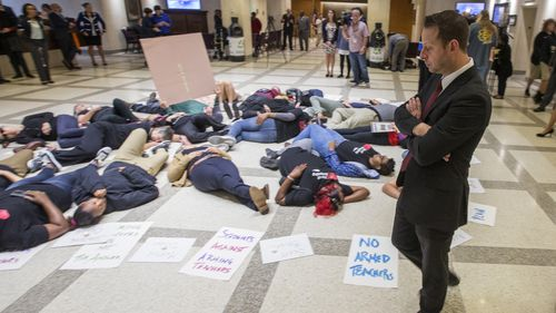 A Florida Rep. surveys a group of 20 students and activists as they stage a die-in on the 4th floor rotunda between the House and Senate chambers. Inside, the House took up the school safety bill. (AAP/AP)