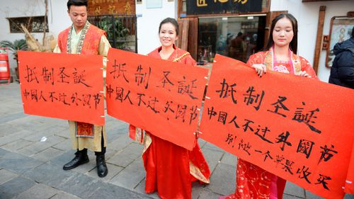 College students wearing traditional Chinese clothing hold slogans in a campaign to boycott Christmas celebrations on a street in Changsha city, central China's Hunan province. (AAP)