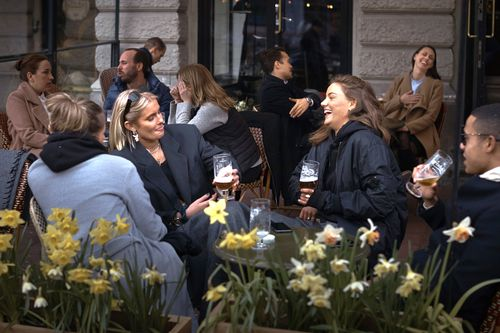 In this April photo, people chat and drink outside a bar in Stockholm, Sweden. Sweden's relatively low-key approach to coronavirus lockdowns captured the world's attention when the pandemic first hit Europe.