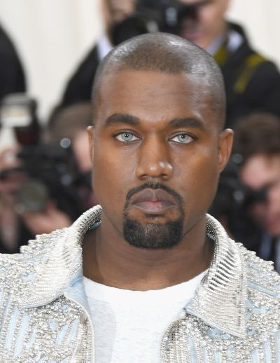 Kanye uses green contacts to pop off his crystal-encrusted jacket.
