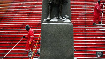 Workers clean off the first accumulation of snow on steps in Times Square in preparation for a large winter storm in New York. (AAP)