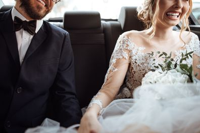 Newlywed bride and groom holding hands in the back seat of their wedding car