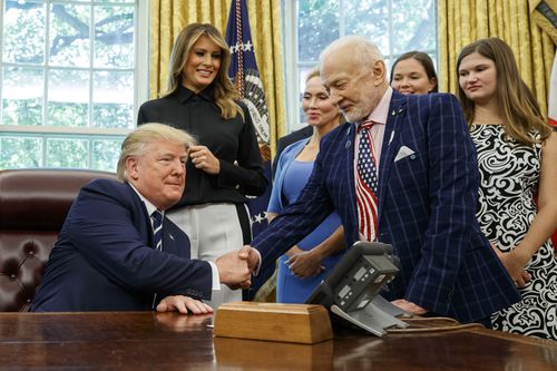 President Donald Trump shakes hands with Apollo 11 astronaut Buzz Aldrin, with first lady Melania Trump.