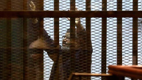 Morsi raises his hands inside a defendants cage in a makeshift courtroom at the national police academy in Cairo in 2015.