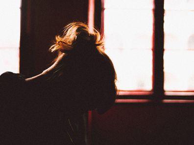 Woman in shadow sitting next to darkened window