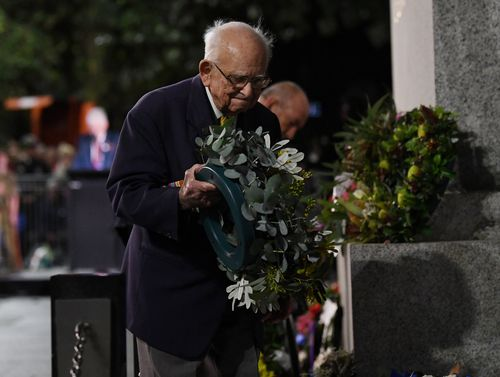 Wally Smith moves a floral tribute during the Anzac Day dawn service at Martin Place in Sydney. (9NEWS)
