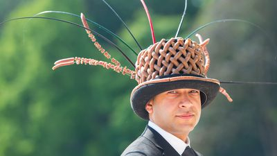 <p> Yaseen Ali-Choudhrey wears a hat made out of peperami sausages during Ladies Day. (AAP) </p>