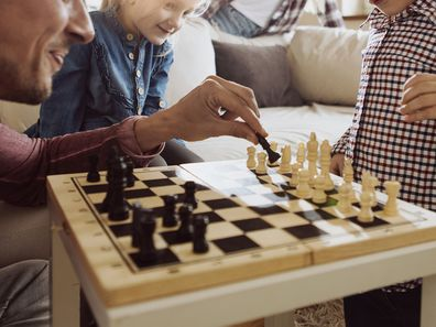 Young family enjoying time at home playing chess together