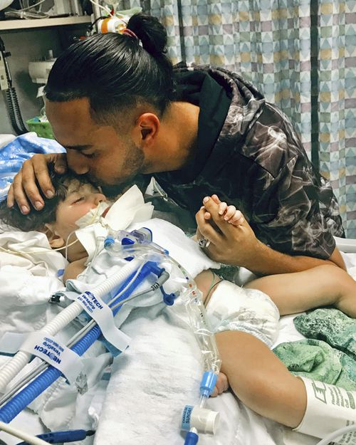 Ali Hassan kissing his dying 2-year-old son Abdullah in a Sacramento hospital. The boy's Yemeni mother, blocked by the Trump administration's travel ban, has won her fight for a waiver that would allow her to travel to California to see her son.