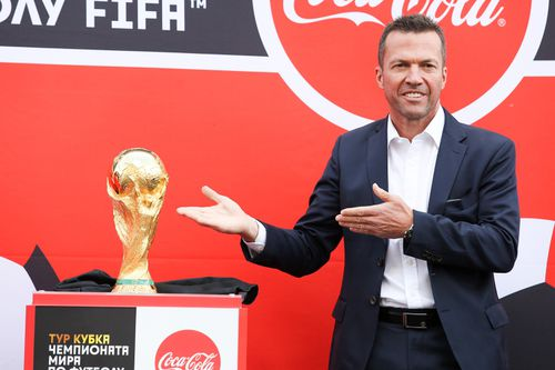 Former German soccer star Lothar Matthaus holds up the trophy during a ceremony to welcome the FIFA World Cup trophy at Manezh Square in Moscow. Picture: AAP