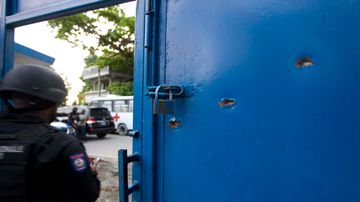 Bullet holes pierce the main gate of the Civil Prison after the mutiny. (AAP)