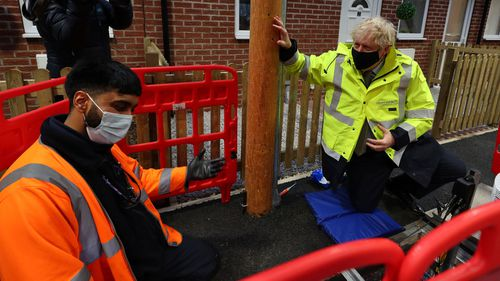 Prime Minister Boris Johnson meets apprentice Zuber Shaikh (L), who is demonstrating groundwork laying during a visit to the Openreach L and D Training Centre in In Bolton on December 18, 2020 in Manchester, England.