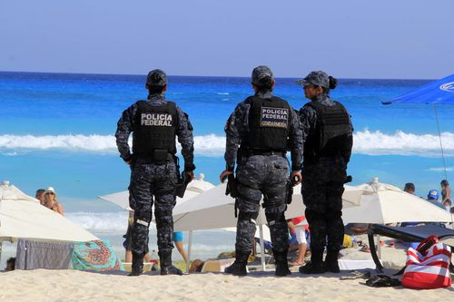 Troops patrol Cancun's beaches, but authorities appear powerless to stop the escalating bloodshed. (AAP)