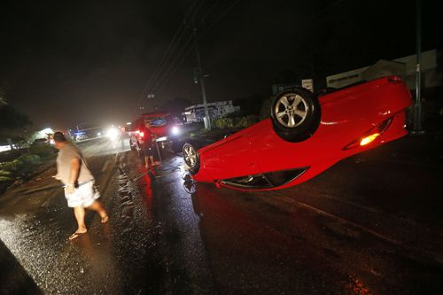 People tend to a car that flipped over on Cape Coral Parkway during Hurricane Irma. (AP)
