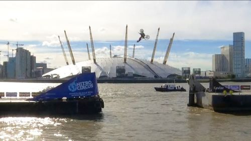 Action sports performer Travis Pastrana performs a backflip on a motorbike between two barges on the river Thames. (Reuters)