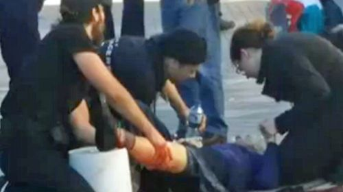 Bystanders rush to help a woman hit by a ricocheting bullet.