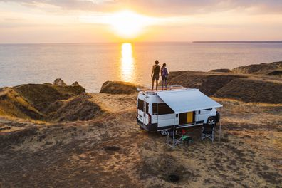 Couple on roof of camper van watching sunset.