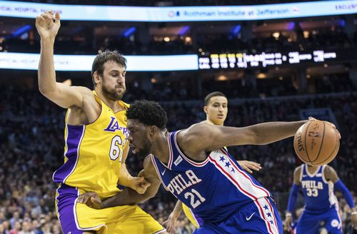 Philadelphia 76ers Joel Embiid, (front right) of Cameroon, makes his move against Los Angeles Lakers Andrew Bogut, left, of Australia, during the second half of an NBA basketball game in December last year. (AAP)