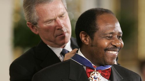 President Bush awards Paul Rusesabagina, who sheltered people at a hotel he managed during the 1994 Rwandan genocide, the Presidential Medal of Freedom Award in the East Room of the White House, in Washington (Photo: Nov, 2005)