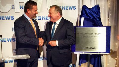 Hitch is presented with the plaque. (9NEWS)