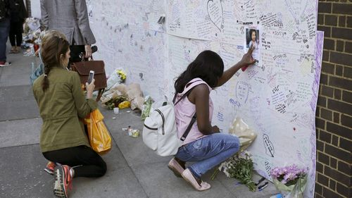 A woman touches a missing poster for 12-year-old Jessica Urbano on a tribute wall after laying flowers on the side of Latymer Community Church next to the fire-gutted Grenfell Tower in London. (AP)