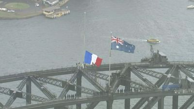 The French flag replaced the New South Wales flag above the bridge at 11am today. Following Commonwealth protocols, the flag is raised at full and not half-mast. (9NEWS)