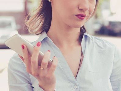 Woman holding phone, looking unimpressed