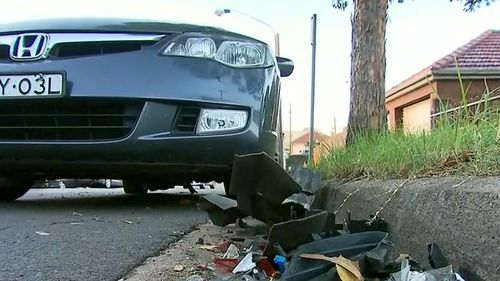 The gutter surrounding the crash was filled with wreckage from both the parked car and the Mitsubishi Magna.