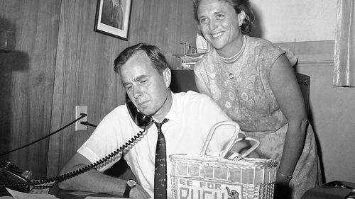 In this June 6, 1964, file photo George H.W. Bush, candidate for the Republican nomination for the US Senate, gets returns by phone at his headquarters in Houston, as his wife Barbara, smiles at the news.