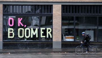 "A man bikes past sticky notes arranged to display the phrase ""OK Boomer"" in a window of a business in Portland, Oregon."