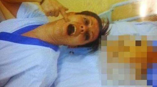 Daniele Poggiali seen here making faces next to the body of an apparently dead woman. (Supplied)