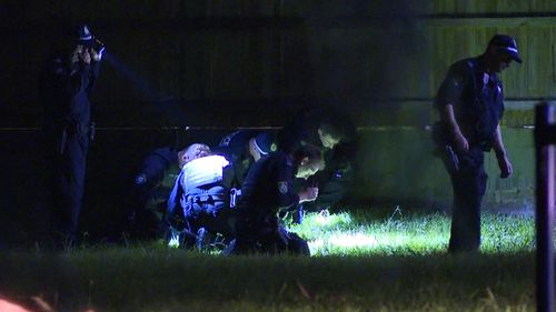 Officers search the scene for evidence.
