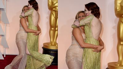 Actresses Jennifer Aniston and Emma Stone embrace in a cheeky hug. (Getty)