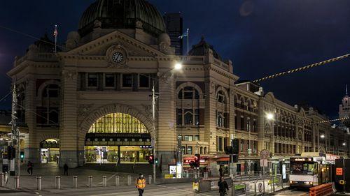 People crossing Flinders Street amid lockdown in Melbourne, Australia.