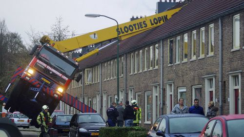 The man jumped to safety as the crane toppled into homes. (AAP)