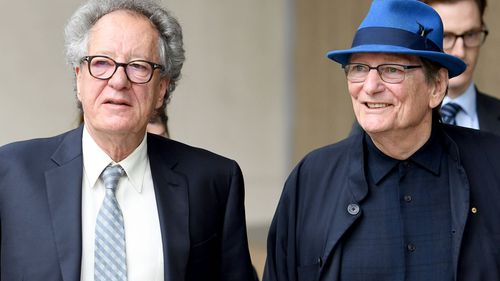 Actor Geoffrey Rush arrives with acclaimed Australian director Fred Schepisi at the Federal Court in Sydney.