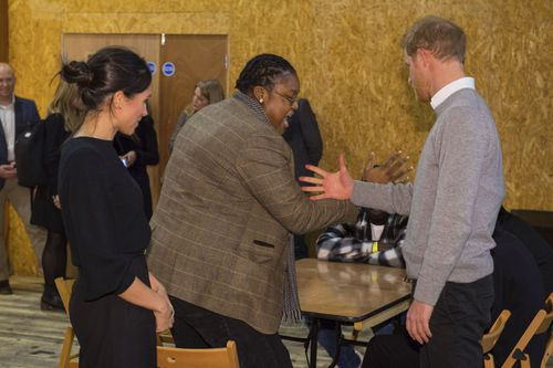 Britain's Prince Harry, right, and his fiancee Meghan Markle, left, meet radio DJ Remi Aderemi during a visit to the Reprezent 107.3 FM. (AAP)