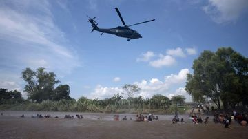 A Mexican Federal Police helicopter flies close to the Suchiate River that connects Mexico and Guatemala, in order to create a downwash force to discourage a new group of Central American migrants bound for the U.S border.