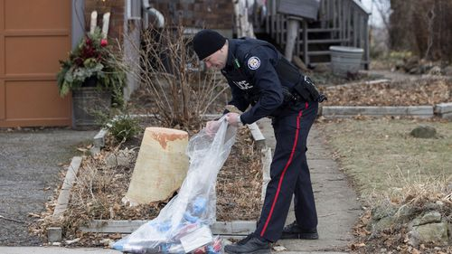 A police officer investigates outside a house on Mallory Crescent in Toronto, where Bruce McArthur did landscape work,