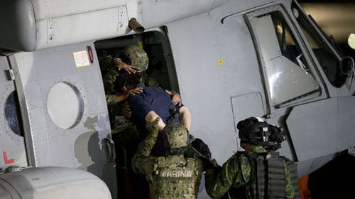 Guzman is loaded into the helicopter for his flight to prison. (AAP)