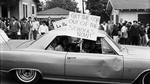 "This March 1968 photo provided by the UCLA Chicano Studies Research Centre, protesters in a car drive by with a sign that reads ""Get the Cops Out of the Schools Now!"" during a walkout by students at Theodore Roosevelt High School in Los Angeles."