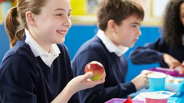 School kids eating lunch, student holding apple
