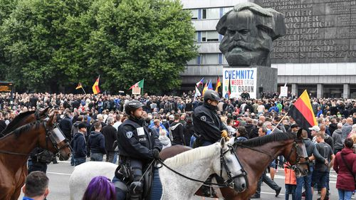 Mounted police surround a protest beneath a statue of Karl Marx in Chemnitz.